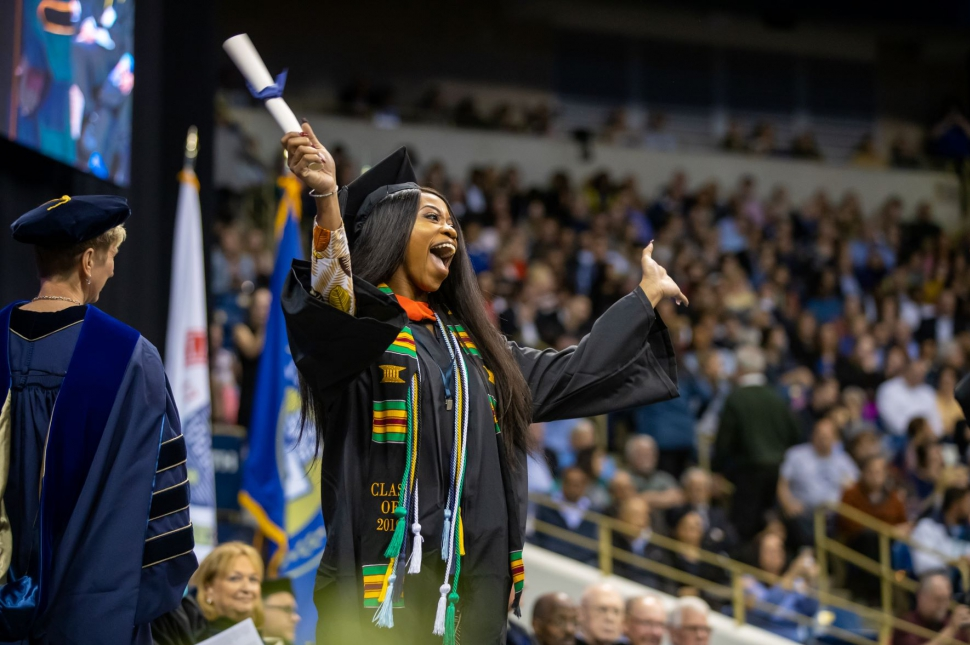Woman celebrating as she receives her diploma.