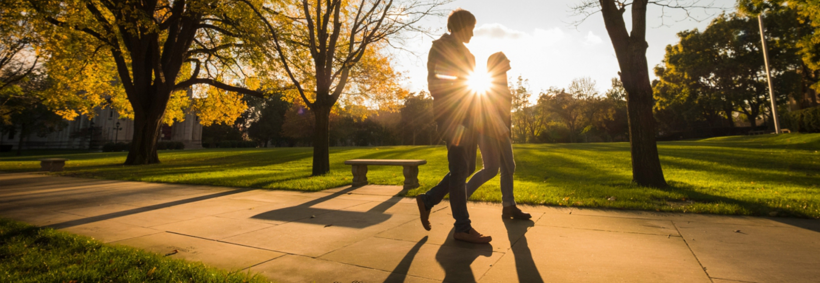 Two students walking in the sunshine on campus